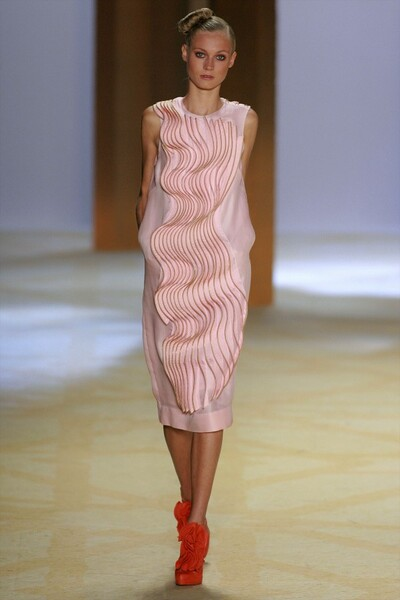 women in fashion show in pink shift dress with large squiggly design down front. she wears tall red shoes with large flowers.