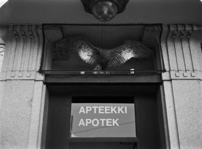Kotka-Apteekin dokumentointi, sisäänkäynnin yläpuolella kyltti Apteekki Apotek ja sen yläpuolella metallinen kotkaveistos siivet levällään. Lönnrotinkatu 9:ssä Albert Nybergin 1908-10 suunnittelemassa myöhäisjugendia edustavassa talossa sijaitseva kulmahuoneiston apteekki.  Apteekin interiöörin suojelusta käytiin pitkällinen kiista vuosina 1996 - 2004. Korkein hallinto-oikeus hylkäsi suojelupäätöksen.
