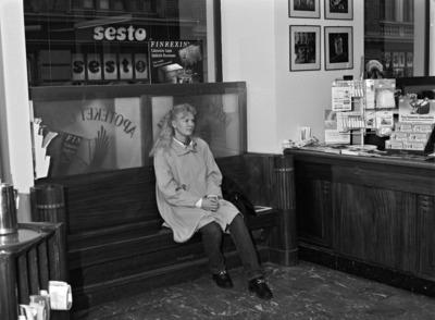 Kotka-Apteekin dokumentointi. Apteekin myyntitila, puinen ikkunasyvennykseen upotettu sohva, myyntitiski, nuori naisasiakas istumassa sohvalla. Näyteikkunassa lasinen paneeli, jossa teksti: 'Kotka apteekki apotek örnen'. Lönnrotinkatu 9:ssä Albert Nybergin 1908-10 suunnittelemassa myöhäisjugendia edustavassa talossa sijaitseva kulmahuoneiston apteekki.  Apteekin interiöörin suojelusta käytiin pitkällinen kiista vuosina 1996 - 2004. Korkein hallinto-oikeus hylkäsi suojelupäätöksen.