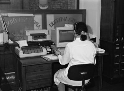 Kotka-Apteekin dokumentointi. Apteekin työntekijä istuu pöydän ääressä ja työskentelee tietokoneella. Näyteikkunassa lasinen paneeli, jossa teksti: 'Kotka apteekki apotek örnen'. Lönnrotinkatu 9:ssä Albert Nybergin 1908-10 suunnittelemassa myöhäisjugendia edustavassa talossa sijaitseva kulmahuoneiston apteekki.  Apteekin interiöörin suojelusta käytiin pitkällinen kiista vuosina 1996 - 2004. Korkein hallinto-oikeus hylkäsi suojelupäätöksen.