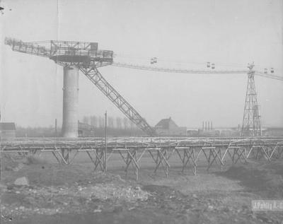 Kabelbaan staatsmijn Maurits. V.l.n.r. het hoofdventilatorengebouw, schachtbok en losvloer schac te Geleenht I, wasserij I en daarvoor de tijdelijke schachtbok II. Voor het machinegebouw het tijdelijke ophaalgebouwtje schacht II (later II-B) . Op de voorgrond de tijdelijke steenstortbrug. Opname uit oktober 1925  van de firma J. Pohling A-G.