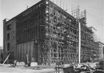 """De fosfaatloods in aanbouw op het Stikstofbindingsbedrijf (SBB) te Geleen. Deze loods werd gebouwd door het aannemersbedrijf """" Bouwnijverheid."""" De foto is gemaakt in juli 1951 door Jaap d' Oliveira uit Amsterdam."""