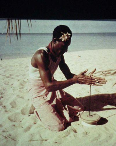 Reeks Aardrijkskunde: kinderspel over de hele wereld, hoort bij de tentoonstelling over kinderspel: een eilandbewoner laat een tol draaien, de tol wordt gebruikt als ritueel (Nieuw-Guinea)