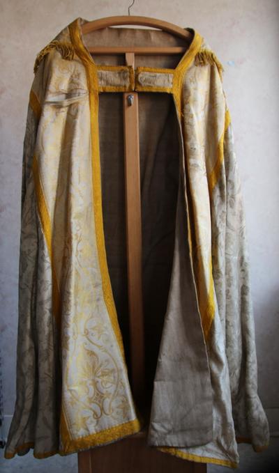 een grijze koorkap met goudkleurige print