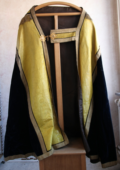 een zwarte koorkap met gele strepen