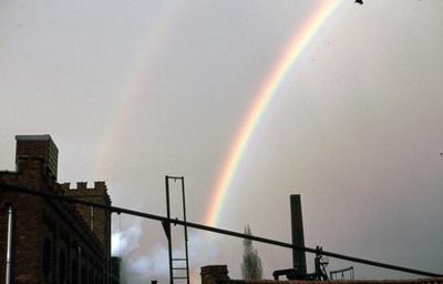Zicht op de bovenkant van de mouterij van Roye met regenboog