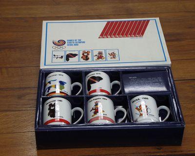 Doos in karton met 5 drinkbekers met logo's Olympische Spelen, verkocht tijdens XXIV Olympiade in Seoul 1988