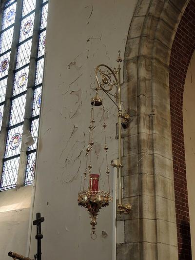Zwaar versierde godslamp aan gekrulde wandarm