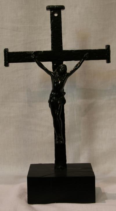 een zwart kruisbeeld op sokkel