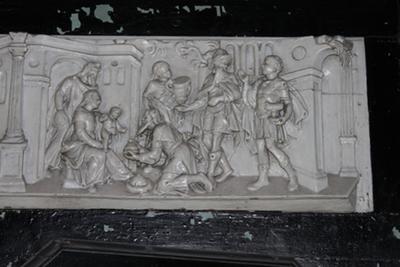 Een houten reliëf, wit geschilderd