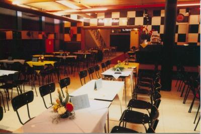 Stoelen en tafels in de Corso met zicht op de entree en de bar