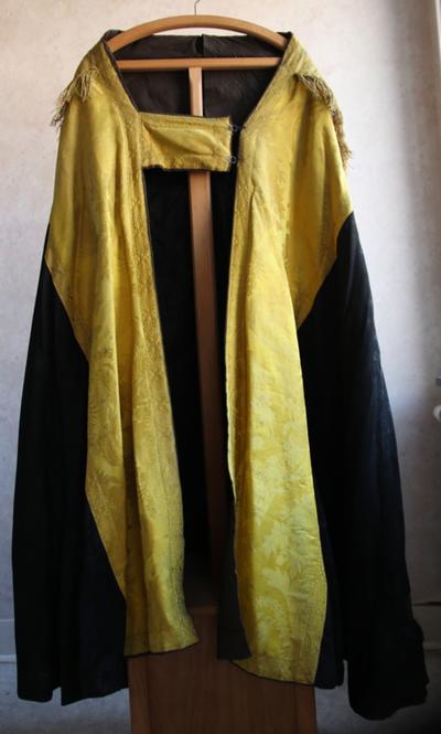 twee zwarte koorkappen met gele banden