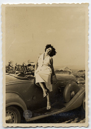 Muller sentada na porta dun coche descapotable