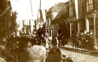 De Jan van Schaffelaarfeesten: feestelijkheden ter gelegenheid van de onthulling van het standbeeld van Jan van Schaffelaar. Optocht in de Jan van Schaffelaarstraat. Op de achtergrond de woning van Jan Mulder, rijksontvanger, later Broekhuis Herenkleding. In de 19e eeuw was in dit pand de Meisjeskostschool gevestigd. De schuur links van dit huis hoorde mogelijk bij het pand van Tijmen Fikse, landbouwer.