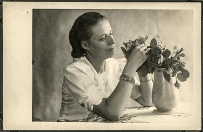 Portret kobiety układającej kwiaty w wazonie