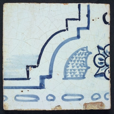 Tussenhoektegel van tegeltableau blauw, wit fond, twee aaneensluitende bijbelse taferelen, met bloemmotief en deel vloer of lucht