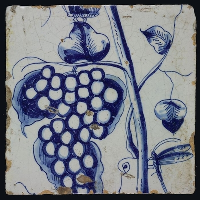Blauwe druiventrostegel met stam, libelle en vlinder, bladeren en ranken behorend bij schoorsteenpilaster met 13 tegels, boom van druiventrossen met vogels, insecten, graan en bladeren