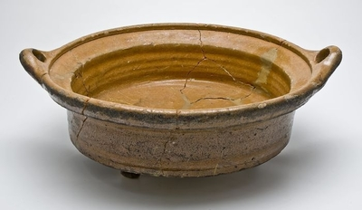 Aardewerk kookpot op drie poten, laag en wijd model met twee schuine haakoren