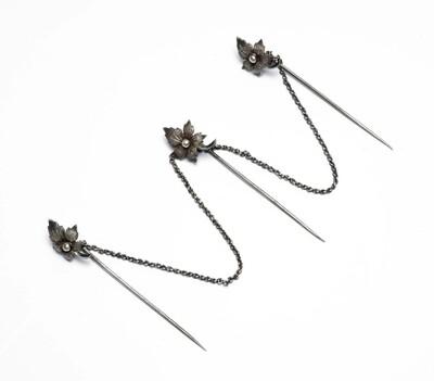 Drie door zilveren een ketting aan elkaar verbonden kabajaspelden