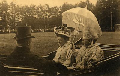 oijtoer van de koninklijke familie 31 augustus 1909. De koets passeert een voetbalveld, waarschijnlijk van A.G.O.V.V. oechts met parasol Koningin Wilhelmina, links Prins Hendrik