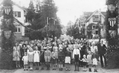 Groep bewoners van de Piet Joubertstraat tijdens de viering van de bevrijdingsfeesten na de Bevrijding van Apeldoorn op 17 april 1945. Gezien vanaf de uitmonding op de noolaan, in noordeijke richting