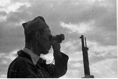 Guaita republicà inspeccionant el terrenys amb uns binoculars de campanya, al front [del Centre]