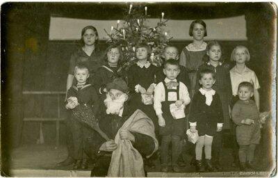Bērni pie Ziemassvētku eglītes