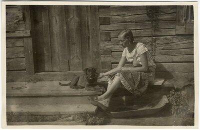 Rembates pagasts. Sieviete ar kucēnu pie Ogresziedu māju klēts lieveņa