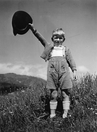 Kinderbilder. Kleiner Junge in Tracht, seinen Hut schwenkend