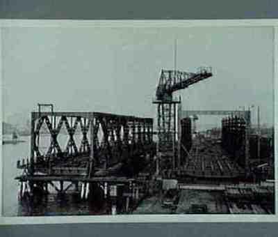 Het bouwen van de 6de en 7de overspanning van de Moerdijkbrug. Tekst op achterzijde foto