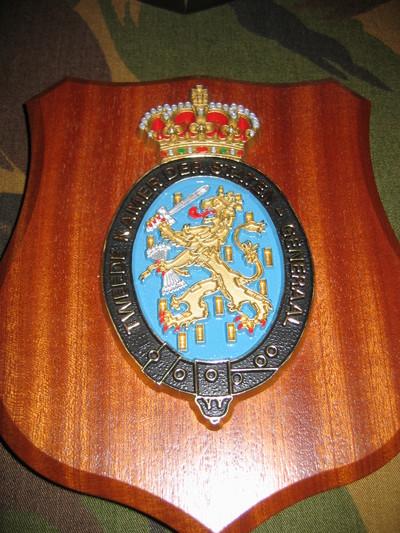 houten ondergrond waarop gehecht een metalen, in kleuren uitgevoerd wapenschild van de Tweede Kamer der Staten-Generaal.