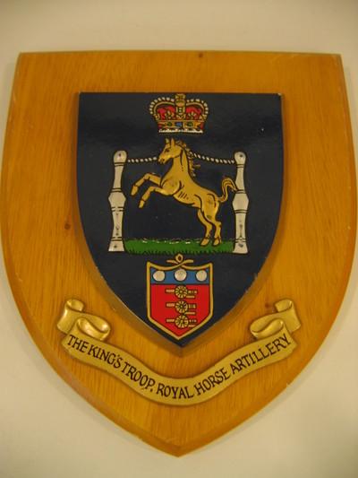 houten ondergrond waarop gehecht een metalen, in kleuren uitgevoerd schildje voorstellend een naar rechts gewend springend paard tussen twee palen boven het wapen van de Royal Artillery, het geheel gedekt door een koningskroon. Onder het schildje een banderol met de woorden: The King's Troop Royal Horse Artillery.
