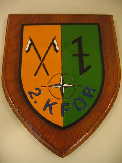 houten ondergrond waarop gehecht een metalen, in kleuren uitgevoerd , staand gedeeld metalen schild (rechts geel; links groen). Op het rechter veld zijn afgebeeld twee gekruiste lansen met wit-zwarte wimpel ( oriflamme ) en op het linker veld een wolfsangel, in het midden, onder de NATO ster boven de letters  2.KFOR .