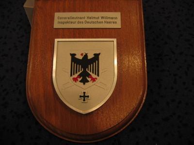schildvormige houten ondergrond waarop bevestigd een metalen mat-zilverkleurig schild beladen met een verkort congruent schild waarop afgebeeld een rood getongde en geklauwde zwarte Duitse adelaar . Het verkorte schild bedekt gedeeltelijk twee gekruiste sabels en rust op een z.g verkort zwartkleurig kruis. Boven het schild op de houten ondergrond bevestigd een zilverkleurig plaatje met het inschrift: ' Generalleutnant Helmut Willmann/ Inspekteur des Deutschen Heeres .