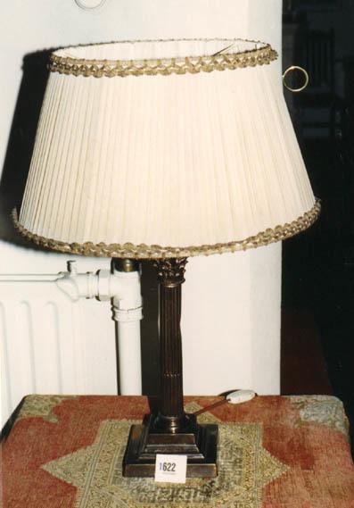 Op een vierkanten plaat staat een kolom welke aan de bovenzijde versierd is met ornamentele versieringen.