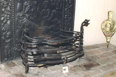 Vuurkorf van buizen in rondingen verbonden aan pootjes welke in krom gebogen knoppen eindigen.