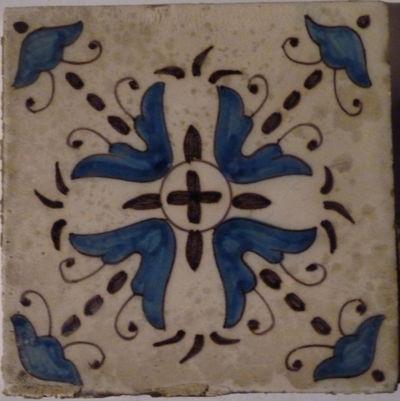 Twee rijen tegels, gedecoreerd met gestileerde bloemmotieven, geschilderd met paarse trek en met blauw ingekleurd, op een witte achtergrond.