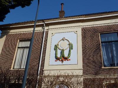 Aan de Dijkstraatzijde van dit monumentale, classicistische hoekpand (Niemeijerstraat 8) bevindt zich op de eerste verdieping een ornament in stucwerk. Het bestaat uit een goud beschilderde cirkel (circa 60 cm in doorsnee) waaraan twee groengeschilderde guirlandes hangen. Daaronder is een rood lint gedrapeerd. Deze en andere villa's in de wijk zijn gevolg van een uitbreidingsplan uit 1874.