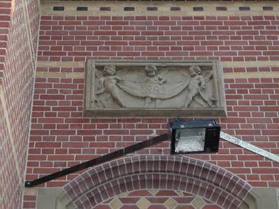 Op de gevelsteen boven de entree staan drie cupido-figuurtjes die een vaan dragen met het jaartal 1882. Cupido, of Amor, is in de klassieke mythologie de god van de liefde en zoon van de godin Venus (of Aphrodite). Vaak wordt hij voorgesteld als een halfbloot, gevleugeld jongetje met pijl en boog.
