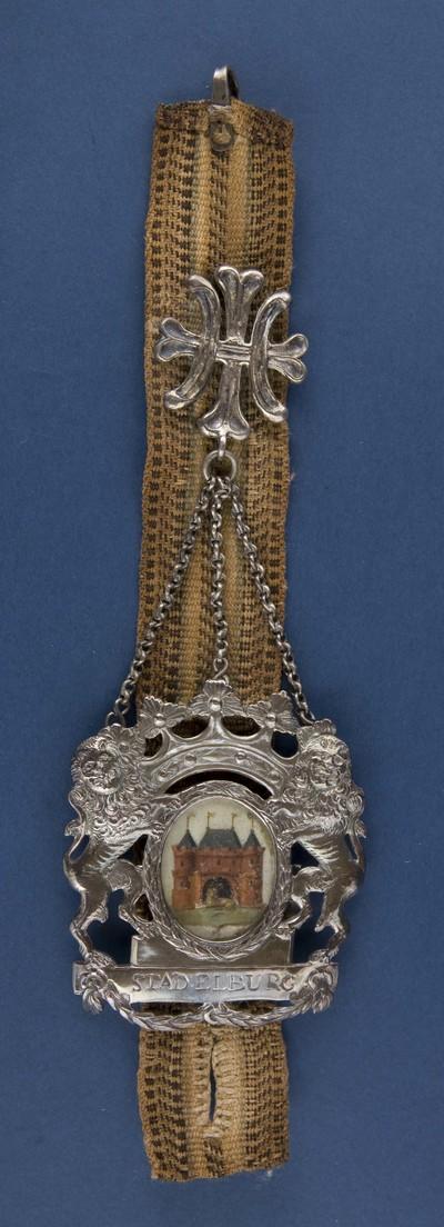 Bodebus van zilver met voorstelling van het stadswapen Elburg, geflankeerd door twee klimmenden leeuwen uitgevoerd in zilver, bevestigd aan een lint, voorzien van merktekens, destijds gedragen door de stadsbode bij officiele gelegenheden