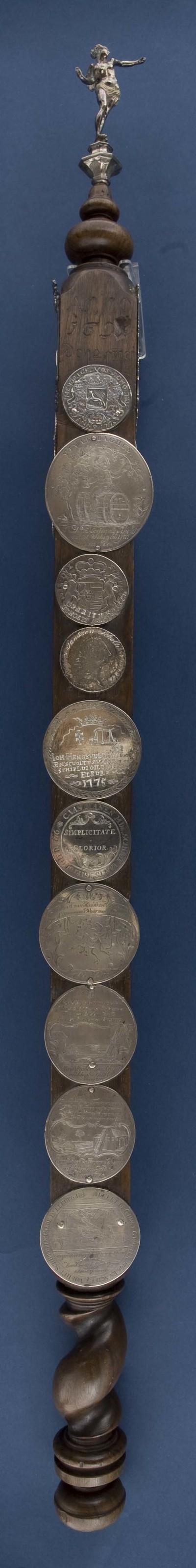 Scepter van notenhout met beeldje van zilver voorstellende de godin Fama, de staf is deels beslagen met zilveren penningen en plaquettes, het hout aan het uiteinde van de staf is gedraaid, voorzien van ingesneden jaartal 25 mei 1697 of 1691, de godin Fama is toegevoegd in 1749