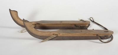 Een paar schaatsen met voetsteunen van hout, glij ijzers en veters ter bevestiging om de voeten