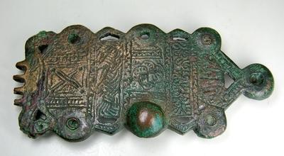 Bronzen beslagplaat van een gordelgesp. Het vlak is in verschillende velden verdeeld met ornamenten in zeer vlak reliëf. Van de oorspronkelijke zeven knopspijkers waarmee de plaat op het leder was bevestigd, was er nog één over.