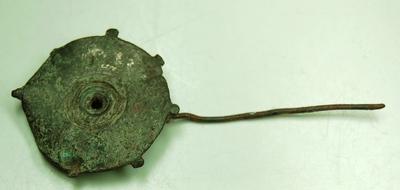 Ronde bronzen schijffibula met 7 uitsteekseltjes. In het midden een gat, waaromheen 3 gekerfde cirkels. Aan deze ronde vorm is een lange speld bevestigd.
