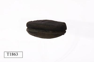 Zwarte mannenpet, gewatteerd, rondom opgenaaid sierband, stoffen klep met leren onderkant.