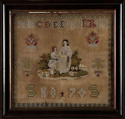 Geborduurde voorstelling; In het midden moeder met kind. Boven letters A t/m M. Er om heen enkele bloemmotieven en rond de gehele voorstelling een geborduurde rand. Onderaan in geborduurde cyfers het jaar 1870.