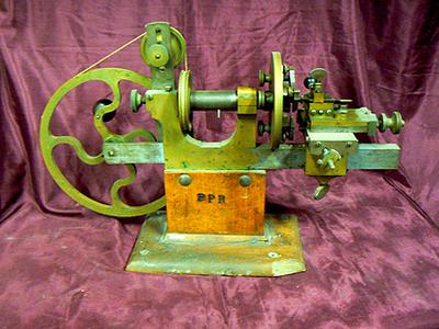 Horlogemakers draaibank. Geheel van messing gemaakte draaibank voor het draaien van tandwielen, gemonteerd op houten voetstuk, draaibank wordt met snaar op loopwiel in beweging gezet. Vervaardiger PPR, datering 1880.