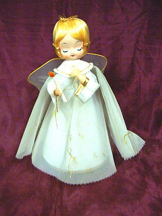 Cilinderspeeldoos, engelfiguur gekleed in witte jurk met gouddraad en strik in het haar, in de rechterhand een kaars. Staat op ronde schijf welke ook het opwindmechniek is, tijdens het spelen draait de pop, de melodie is 'Stille Nacht'. Datering 1950.