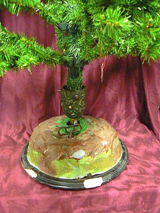 Kerstboomstandaard met cilinderspeelwerk voor een kerstboom. Tijdens het spelen van muziek draait de kerstboom rond. Het speelwerk bevat 2 melodieen 'Stille Nacht' en 'O Denneboom'. Datering 1885-1895.