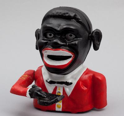 Spaarpot met speelwerk, bestaande uit metalen buste die zijn hand ophoudt. Hierop kan geld worden gelegd dat dan in zijn mond verdwijnt, waarbij ook oren en ogen draaien. Made in Taiwan. Datering 1965.